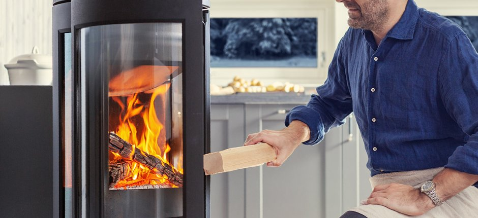 Man put wood in fireplace Photo